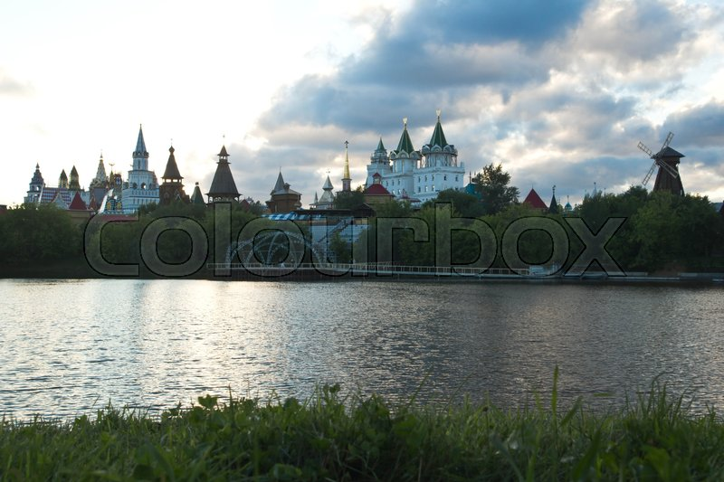 Stock image of 'wooden mill and Kremlin on the banks of the river in the evening '