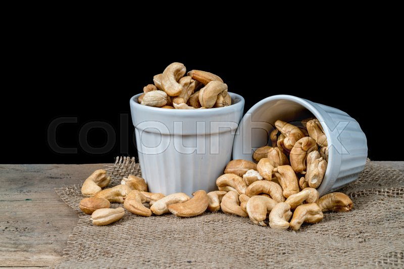 Stock image of 'Cashew nuts in white ceramic cup'