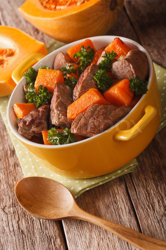 Stock image of 'Stew beef with pumpkin closeup in the pan on the table. vertical\'