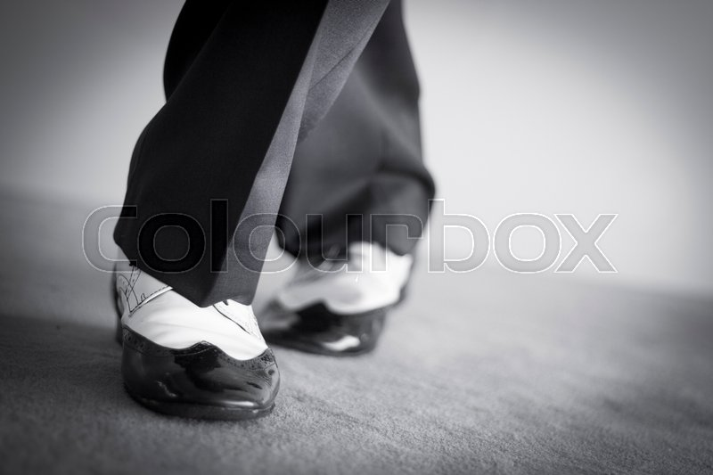 Stock image of 'Male latin and salsa dancer in black and white jazz dancing shoes in light and dark on stage monochrome photo.'
