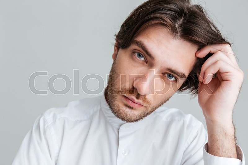 Stock image of 'Close up portrait of a thoughtful young brunette man in white shirt sitting at the table isolated on the gray background'