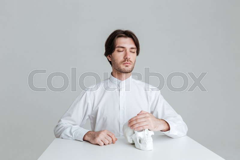 Stock image of 'Man sitting with eyes closed holding fake skull at the table isolated on the gray background'