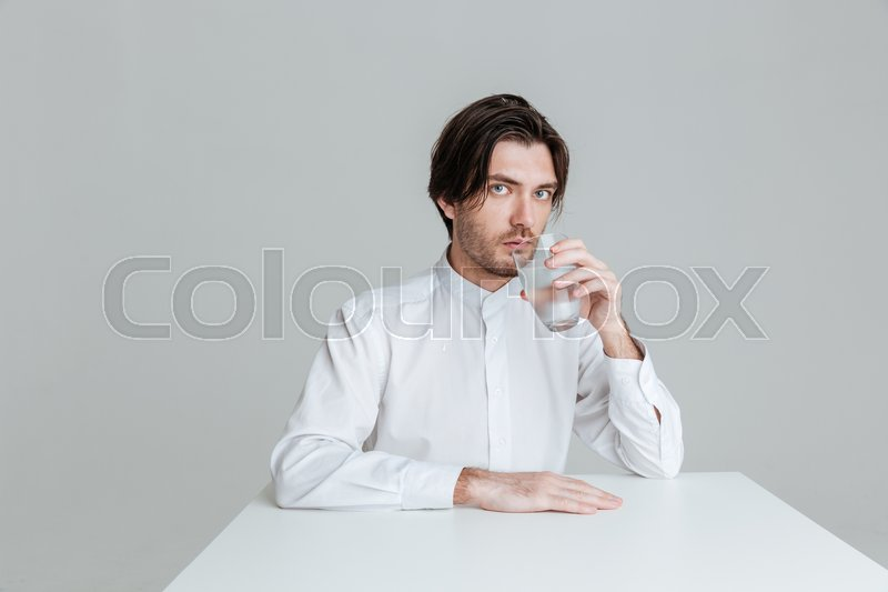 Stock image of 'Handsome young man drinking from water glass while sitting at the table isolated on the gray background'