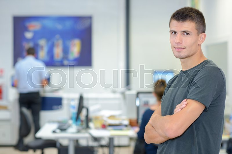 Stock image of 'Young man with arms crossed in computer room'