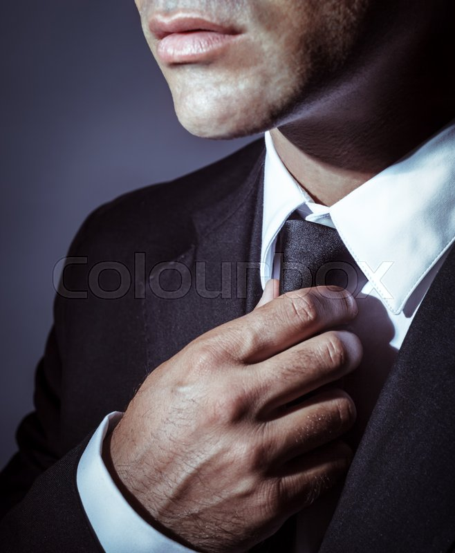 Stock image of 'Closeup photo of a serious businessman wearing stylish black suit and tie over dark background, face part, mens wear fashion concept'