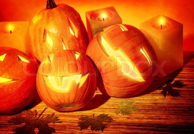 Stock image of 'Closeup photo of a carved pumpkins with scary faces and glowing candles on the table, festive party decoration for Halloween holiday'