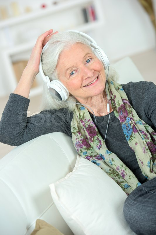 Stock image of 'Senior lady listening to some music'