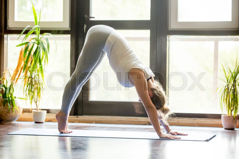 Stock image of 'Full length portrait of attractive young woman working out at home in living room, doing yoga exercise on blue mat, downward facing dog pose, adho mukha svanasana sun salutation pose , side view'