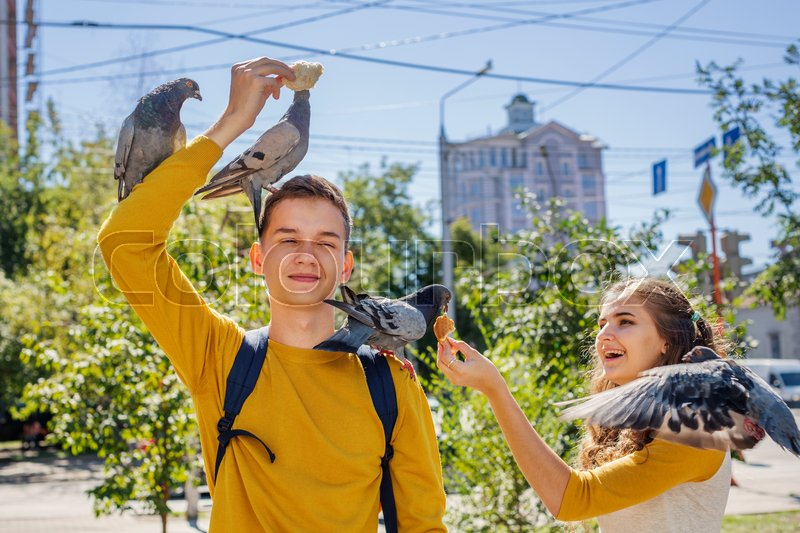 Stock image of 'Couple teenagers feeding pigeons on city street summer day'