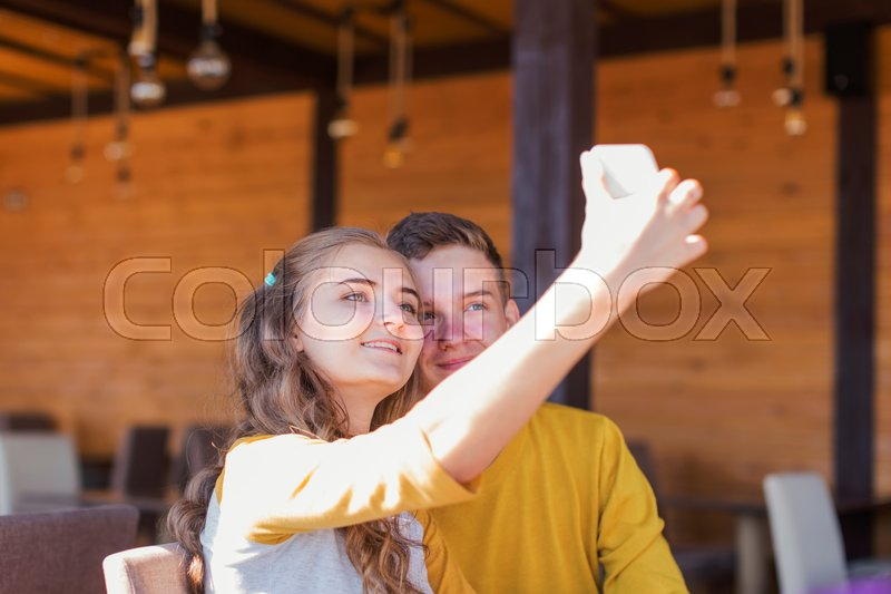 Stock image of 'A couple of teenagers in a summer cafe photographed themselves on the phone'