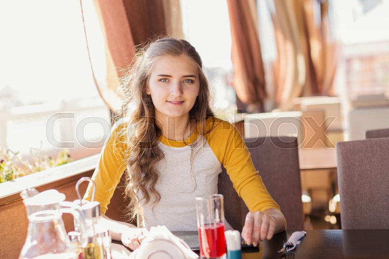 Stock image of 'Teen girl in a summer cafe, horizontal frame'