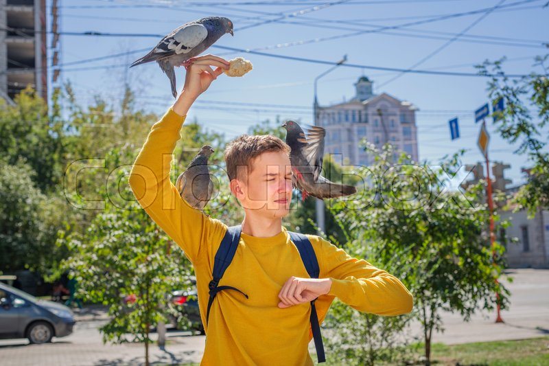 Stock image of 'Teen boy feeds pigeons on city street summer day'