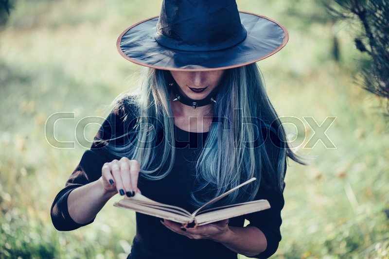 Stock image of 'Young woman in costume of witch reading a book of magic outdoor, close-up, front view. Theme of Halloween and magic'