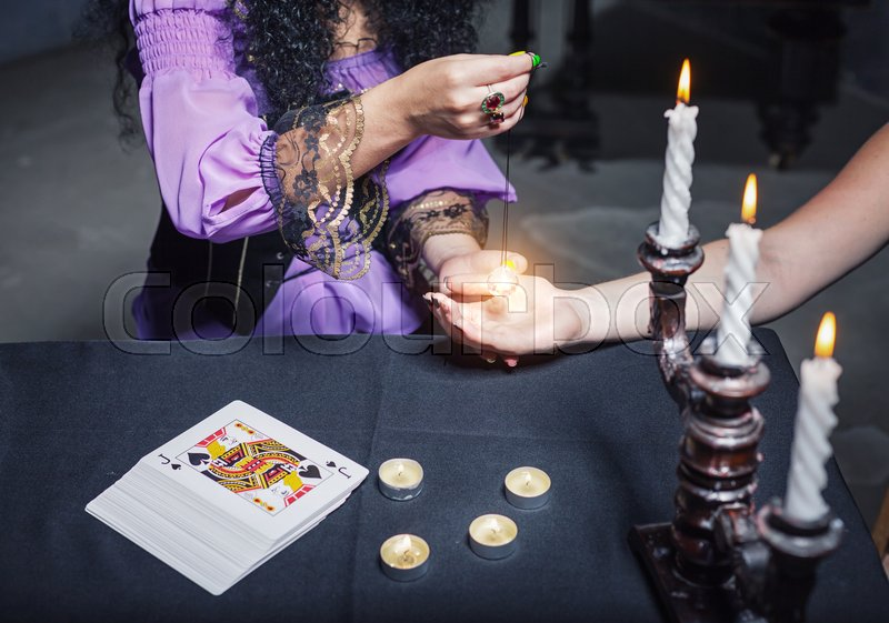 Stock image of 'Sorceress reading somebody's hand using magic crystal'