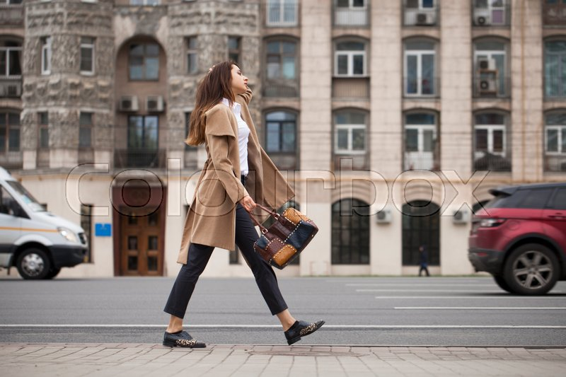 Stock image of 'Young beautiful woman in beige coat with a bag walking on the autumn street'