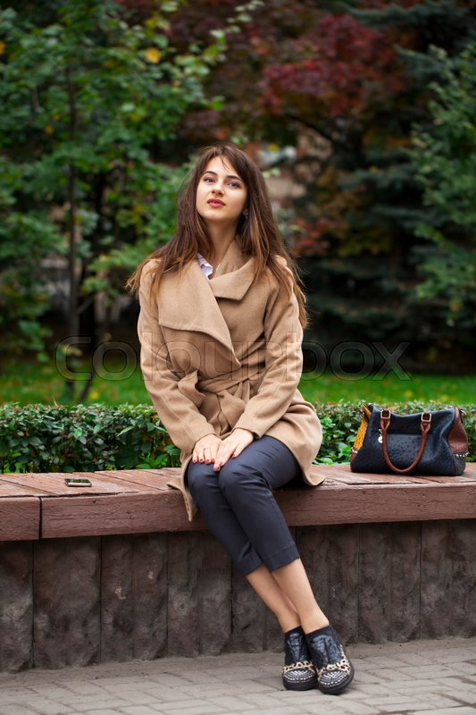 Stock image of 'Young beautiful brunette woman in beige coat sitting on a bench in the autumn park'