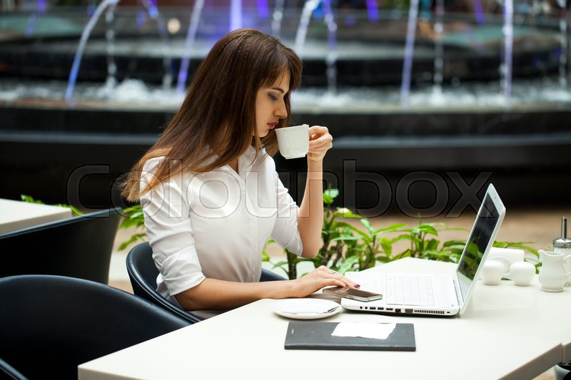 Stock image of 'Young beautiful business woman drinking coffee while sitting in a restaurant'