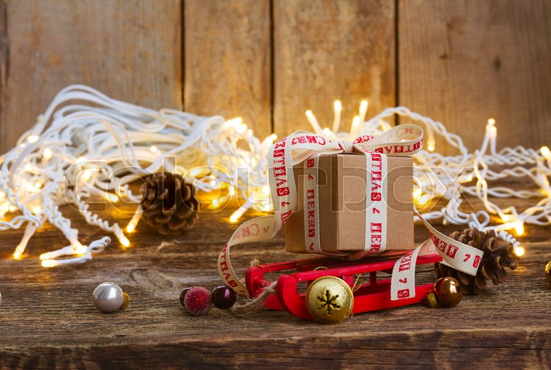 Stock image of 'One handmade gift box on sledge with christmas lights on wooden background'