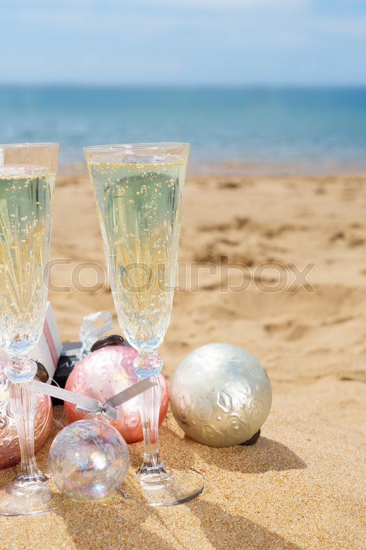 Stock image of 'Two glasses of christmas champagne with christmas gifts and decorations on beach by the sea'