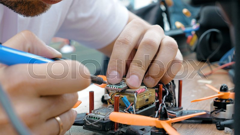 Stock image of 'Close up of man's hands welding details while assembling FPV drone using tools, preparing quadcopter for flight. Repair drone before training process.'