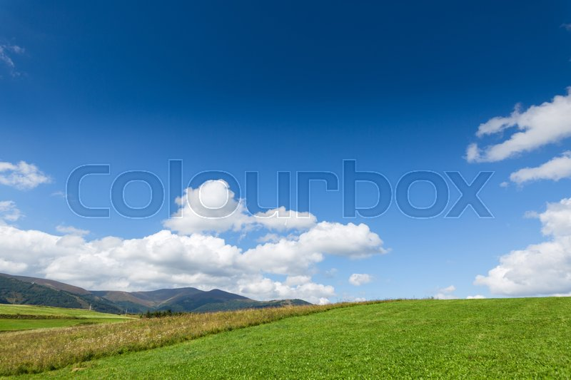 Stock image of 'Green meadow, mountain and blue sky with clouds'