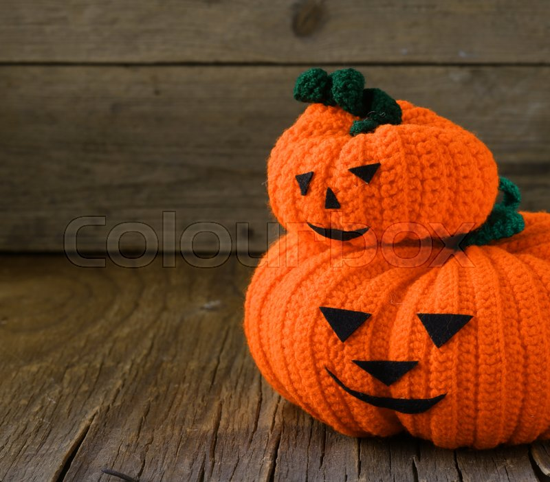 Stock image of 'Knitted pumpkins for Halloween decorations holiday, on a wooden background'