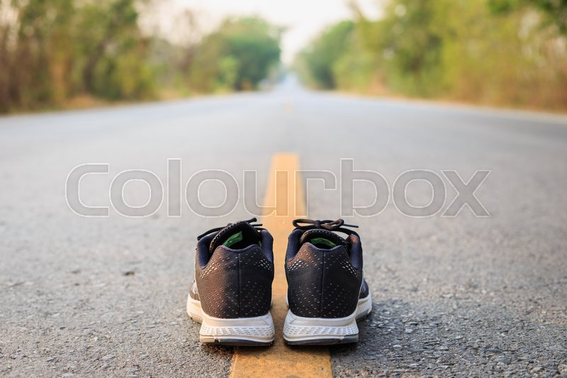 Stock image of 'Close up new black running shoes on asphalt road in morning time'