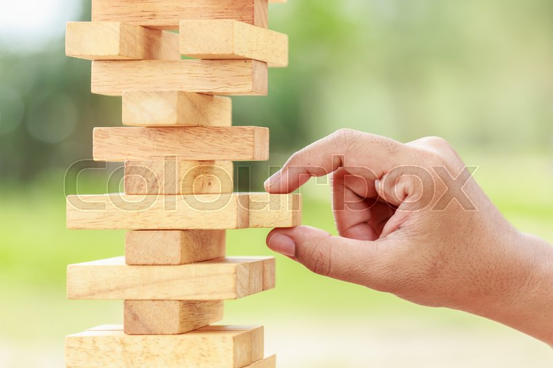 Stock image of 'Close up hand holding blocks wood game (jenga) on blurred green background. Risk concept'
