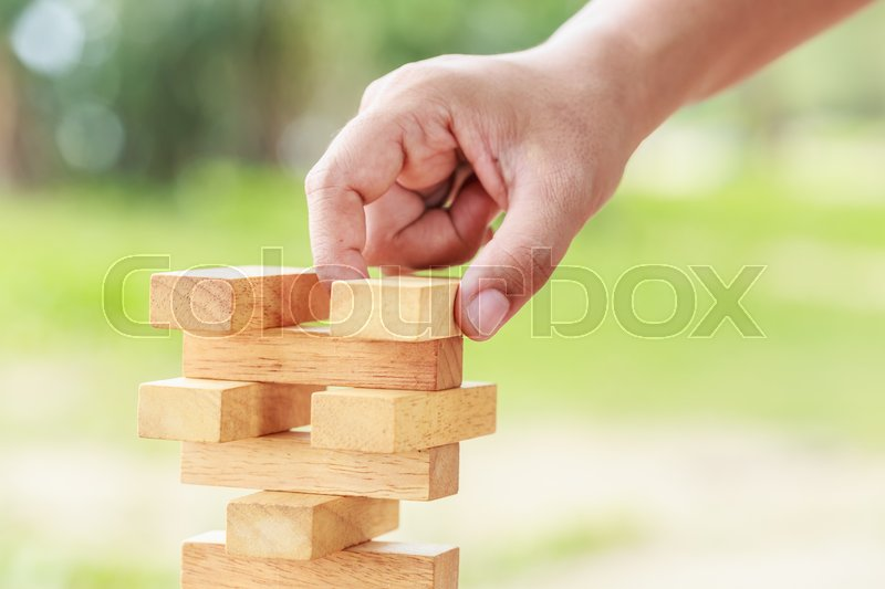 Close up hand holding blocks wood game (jenga) on blurred green background. Risk concept, stock photo