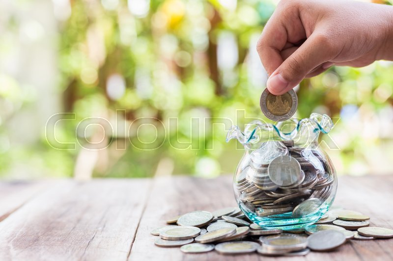 Stock image of 'Close up hand putting coins in money jar. savings concept.'