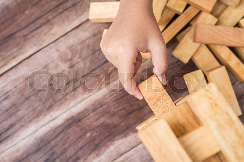 Close up hand holding blocks wood game (jenga) on wooden plank background. Risk concept, stock photo