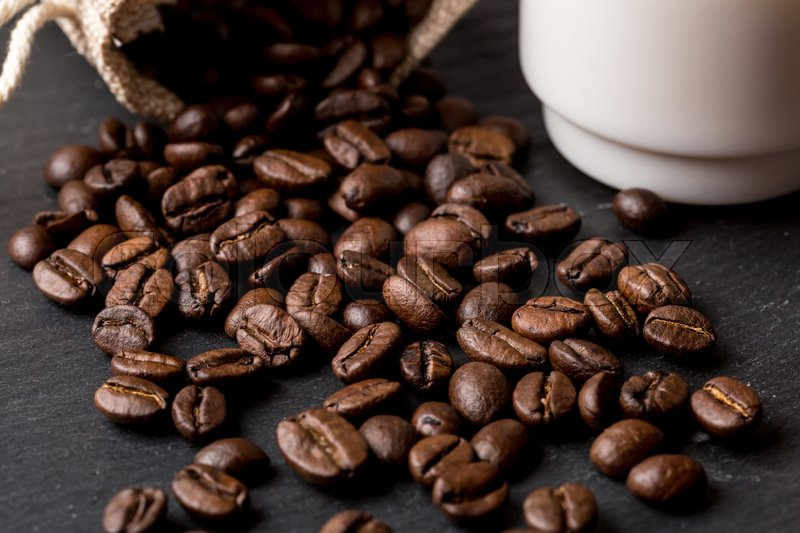 Stock image of 'A cup of coffee with coffe beans as background'