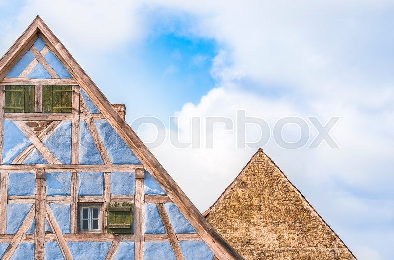 Stock image of 'Architectural details of two lofts from medieval german houses, one with half timbered blue walls, wooden shutters and one with stone wall.'