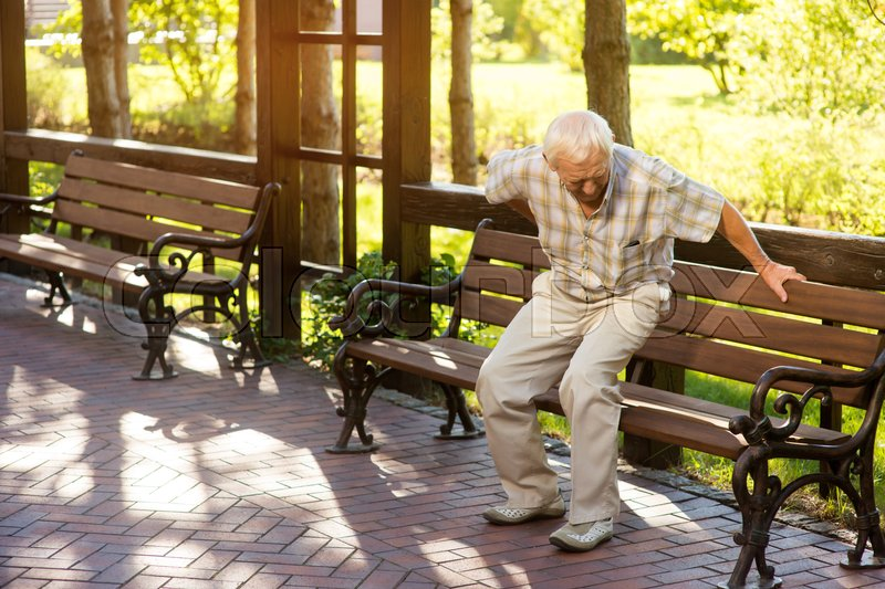Stock image of 'Senior man holding his back. Old male near park bench. Strong pains in spine. Need of medication and therapy.'