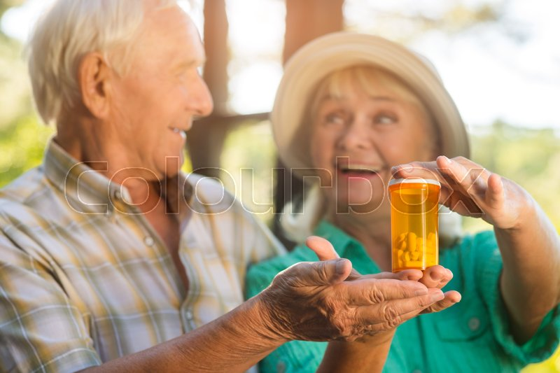Stock image of 'Couple with pill bottle. Smiling senior man and woman. Drug with vitamins and minerals. Restore your health.'