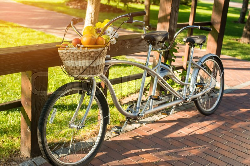Stock image of 'Tandem bicycle in the park. Wicker basket with fruits. Spend weekend in open air. Enjoy rest and save health.'