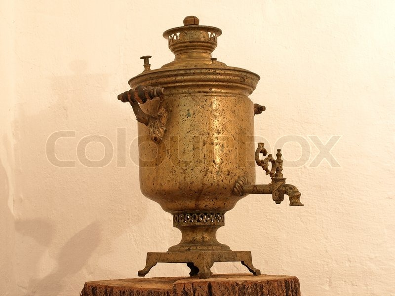 Stock image of 'Old copper samovar against a clay wall.'
