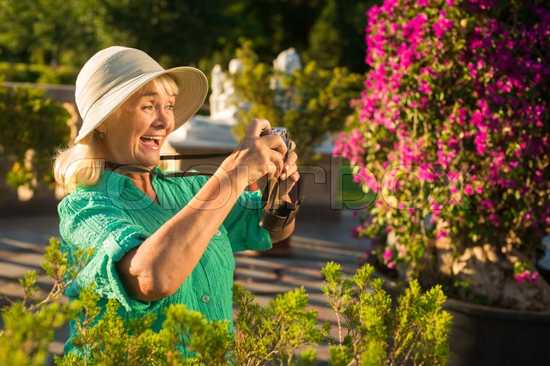 Stock image of 'Senior woman holding camera. Lady in hat is laughing. Find yourself a new hobby. Amazing life around us.'