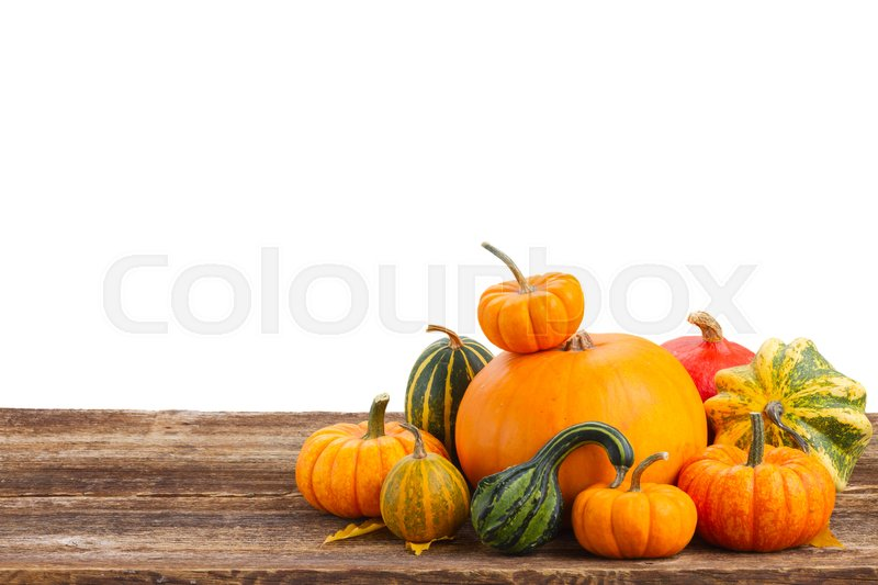 Stock image of 'pile of raw orange pumpkins on wooden table border isolated on white background'