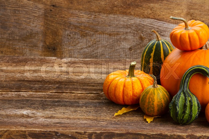 Stock image of 'pile of orange and green pumpkins on wooden rustic table with copy space'