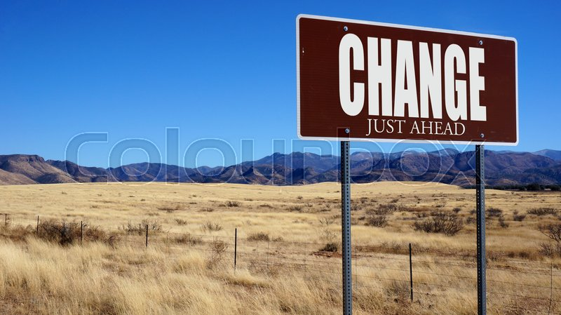 Stock image of 'Change Just Ahead brown road sign with blue sky and wilderness'