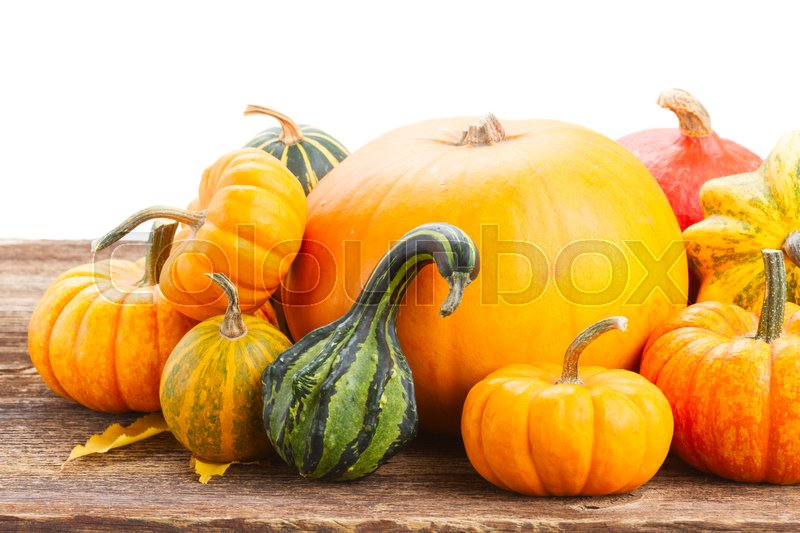 Stock image of 'pile of orange pumpkins on wooden table border isolated on white background'