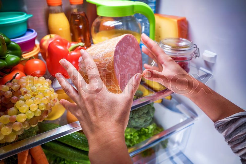 Stock image of 'Human hands reaching for food at night in the open refrigerator'