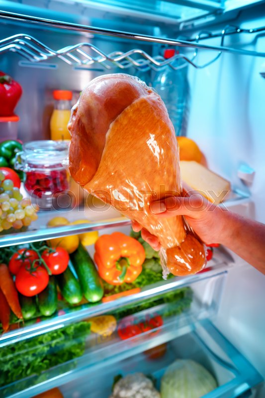 Stock image of 'Human hands reaching for turkey leg food at night in the open refrigerator'