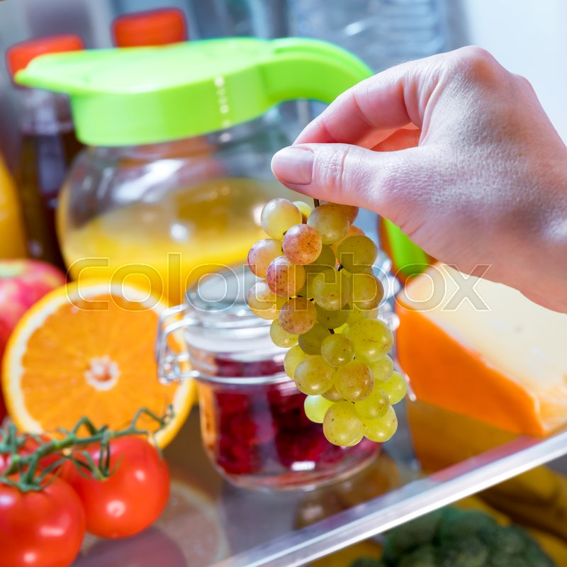 Stock image of 'Woman takes the bunch of grapes from the open refrigerator. Healthy food.'