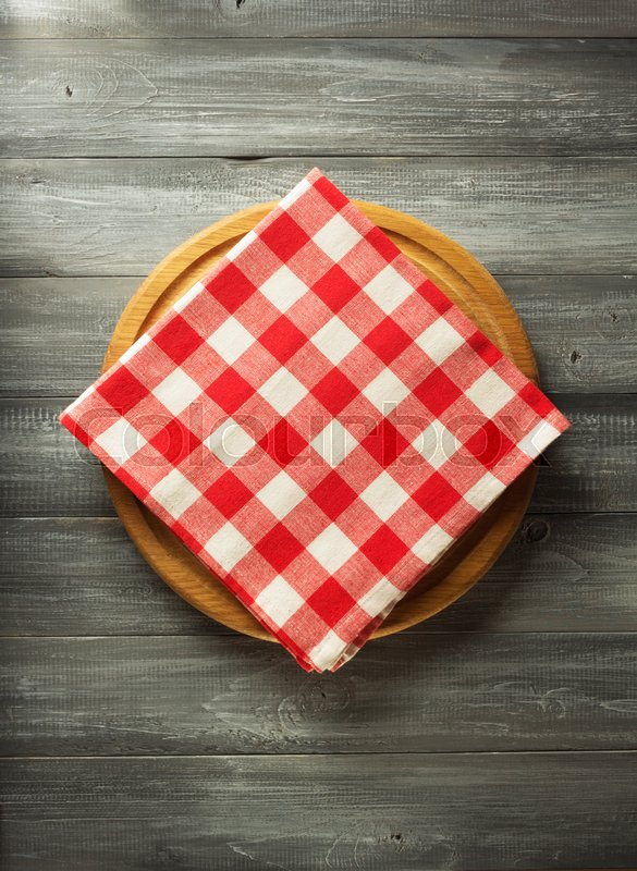Stock image of 'napkin at cutting board on wooden background'