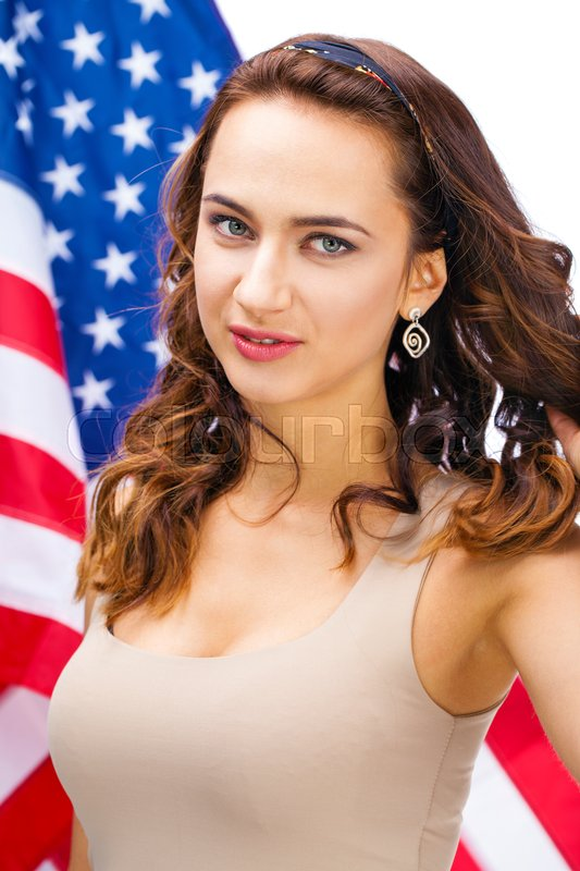 Stock image of 'Portrait of a happy young woman on a background of the American flag'