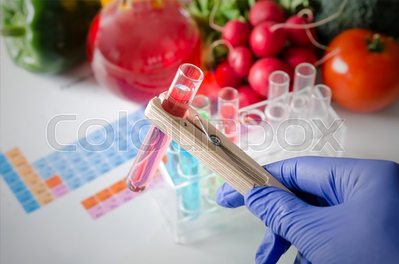 Stock image of 'Analyst in gloves takes test tube. Genetically modified food in lab concept.'