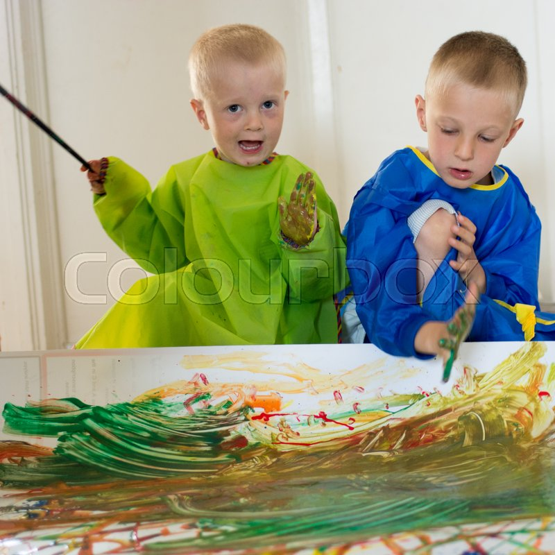 Stock image of 'Children painting with their hands on white paper on the floor'