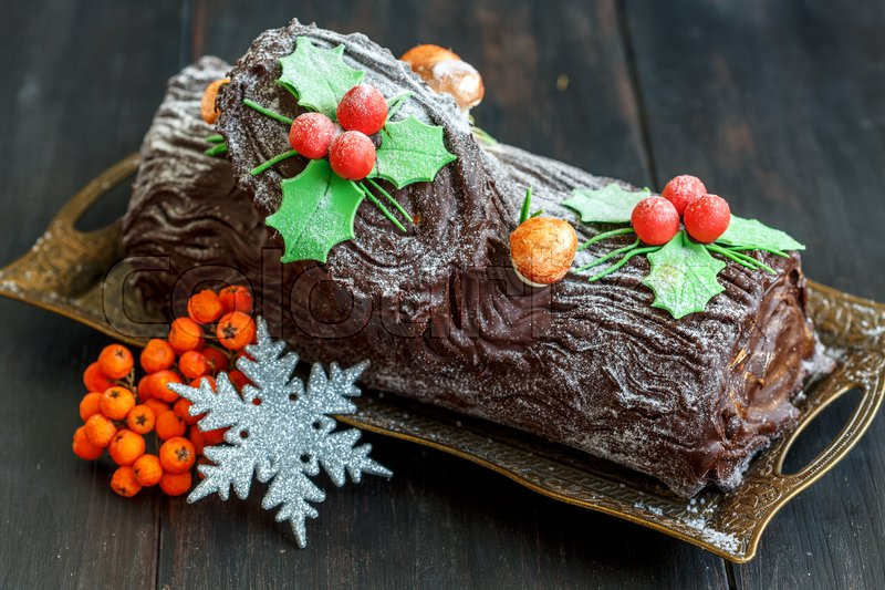 Stock image of 'Christmas chocolate yule log with decor of colored chocolate on a wooden table.'